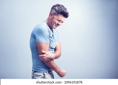People, healthcare and problem concept - close up of man suffering from pain in hand or elbow