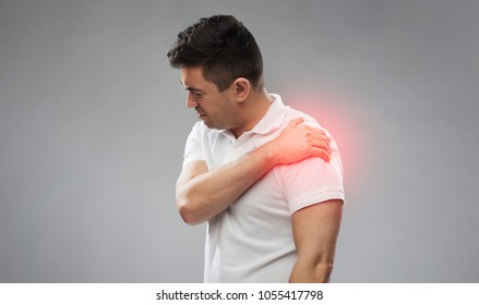 people, healthcare and problem concept - unhappy man suffering from pain in shoulder over gray background