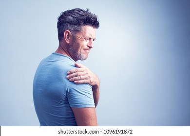 People, healthcare and problem concept - unhappy man suffering from neck or shoulder pain at home