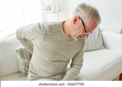 people, healthcare and problem concept - unhappy senior man suffering from pain in back or reins at home