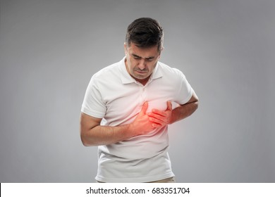 people, healthcare and problem concept - unhappy man suffering from heart ache over gray background