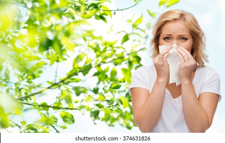 people, healthcare, rhinitis, cold and allergy concept - unhappy woman with paper napkin blowing nose over natural background