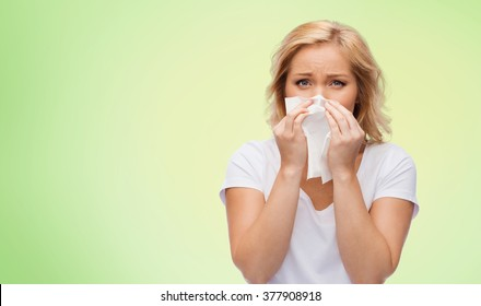 people, healthcare, rhinitis, cold and allergy concept - unhappy woman with paper napkin blowing nose over green natural background