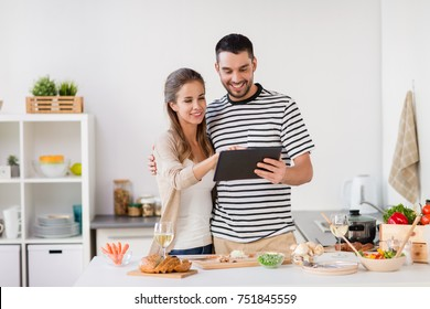 people and healthy eating concept - happy couple with tablet pc computer cooking food at home kitchen