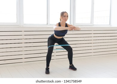 People, healthy and sport concept - Fit woman In sports clothes squatting with band