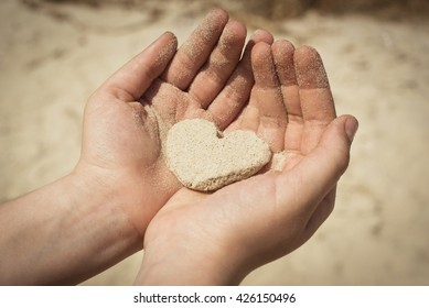 People heart concept. Child's hands holding heart made of sand. Close up. Outdoor shot