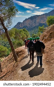 People with helmets hiking in a mountain in Malaga (Spain)
