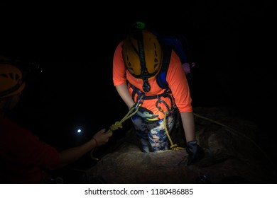 People help each others to climb down of rock cliff in dark cave in Son Dong, the largest cave in the world in UNESCO World Heritage Site Phong Nha-Ke Bang National Park, Quang Binh province, Vietnam