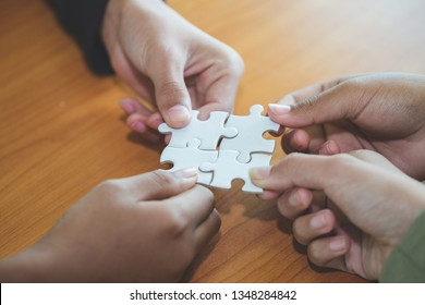 people helping in assembling puzzle, cooperation in decision making, team support in solving problems and corporate group teamwork concept, close up view of hands connecting pieces