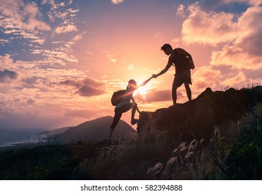 People helping each other hike up a mountain at sunrise.  Giving a helping hand, and active fit lifestyle concept.