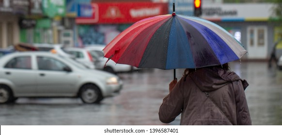 People hide from rain under umbrellas in a rainy day on the street of the city Bad weather concept