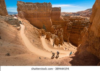 People, hikers, hiking on the trail into the canyon at Bryce Canyon National Park. This hiking trail was named Wall Street part of the hiking trail,  The hiking trail was named Navajo Loop
