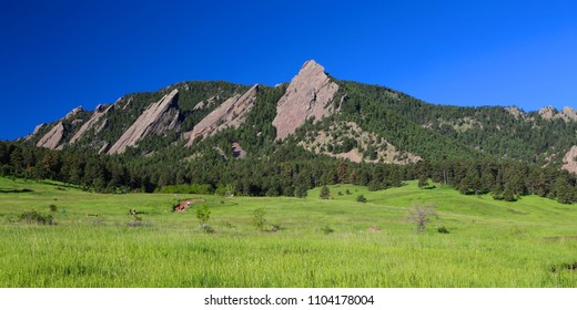 People hiking along the Boulder Flatirons of the Colorado Rocky Mountains in summer