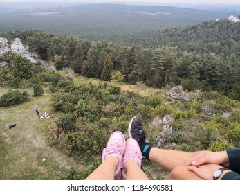 People hiking and climbing in the mountains. Beautiful aerial view. Hikers seen from above. Legs of friends or lovers sitting on the top of the peak. Nature outdoors recreation.