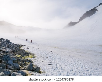 People hiking up and down snow slope of Spigot Peak in mist, Graham Land, Antarctic Peninsula, Antarctica