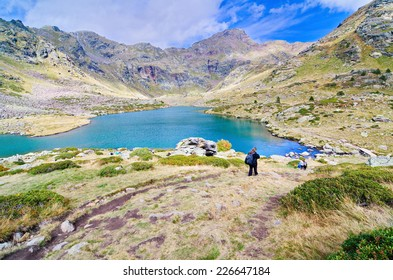 People hiking to Estany Primer - one of the three lakes of Tristaina (Estanys de Tristaina) in Andorra near the Ordino-Arcalis ski resort in the spring