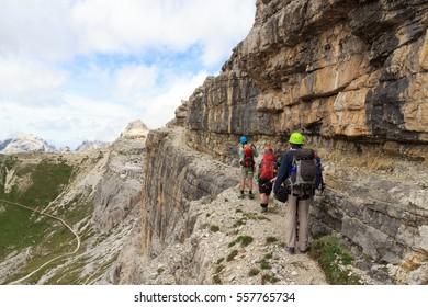 People hiking on via ferrata Alpinisteig in Sexten Dolomites mountains, South Tyrol, Italy