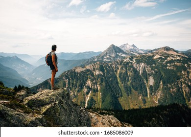 People hiking through the British Columbia mountains in the summer time. Lake in the background. Distant mountains. Beautiful scenery.