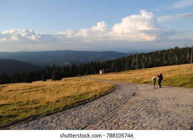People hiking through trail in the moutains during fall season. Beautiful autumn weather on a trip. Sport in nature enviroment. Nature scenery, beautiful landscape, hills and grass, clouds. Blue sky.