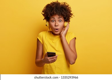 People, hobby, reaction concept. Impressed shocked dark skinned hipster girl surprised to listen audio track with high volume, has headphones on ears and smart phone in hand, isolated over yellow wall