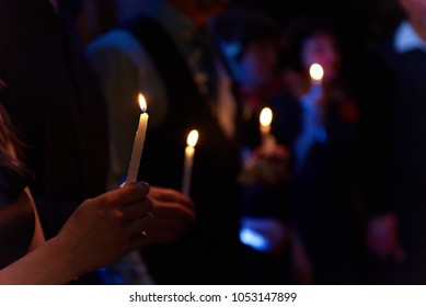 People hold candles light at dark scene