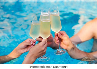 People hold champagne glasses in the pool. Summer pool party