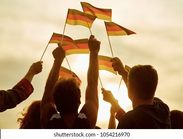 People hold german flags. Silhouette of patriotic deutsch crowd, rear view. Gloving evening sun background.