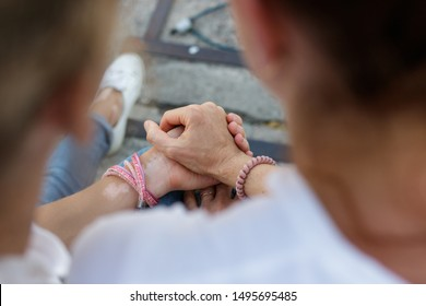 People hold hands outdoors in summer. Close-up. Vitiligo disease on the skin of the hands - skin depigmentation