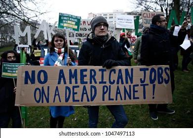People hold placards and shout slogans during a protest against Trump's environmental policy at conference attended by Trump climate advisor Myron Ebell in Brussels, Belgium on Feb. 2017