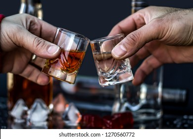 People holding glasses with alcohol and making toast, close-up