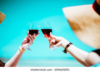 People holding glasses of red wine .wine at a relax party celebration gathering at the beach.Sumer.wine beach two girl.Minimal Summer holidays.