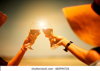 People holding glasses of red wine making a toast at the beach picnic on summer.friends toasting champagne sparkling wine at a relax party celebration gathering at the beach.Sumer.wine beach two girl.