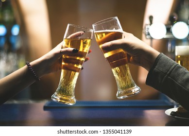 People are holding in hands a glasses with a beer and are clinking.