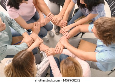 People holding hands together at group therapy session