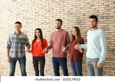 People holding hands together, indoors. Unity concept