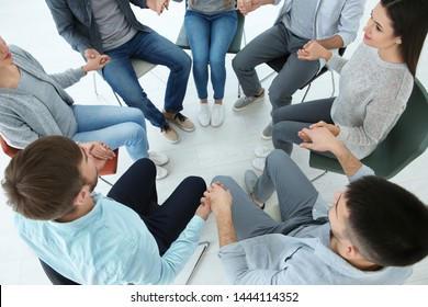 People holding hands together, indoors. Group therapy