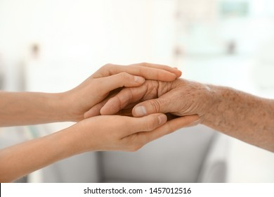 People holding hands together on blurred background, closeup. Help and elderly care concept