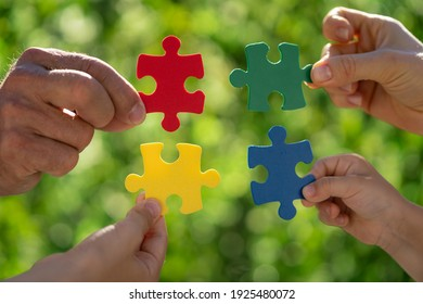 People holding multicolor jigsaw puzzle in hands against green spring blurred background