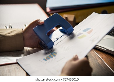 People holding a paper punch with for document file