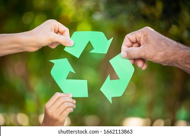People holding recycle symbol against green spring background. Earth day holiday concept.