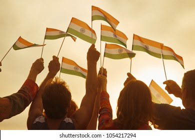 People holding small indian flags. Rally for human rights in India. Patriotic family outdoor. Evening sky background.
