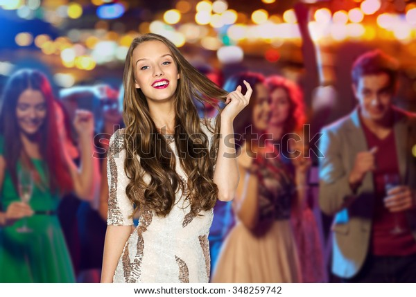 people, holidays, celebration and glamour concept - happy young woman or teen girl in fancy dress with sequins at night club party over crowd and lights background