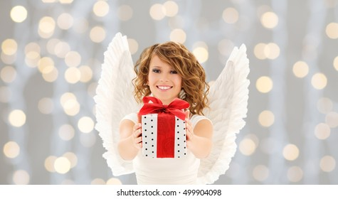 people, holidays, christmas and birthday concept - happy young woman with angel wings holding gift box over lights background