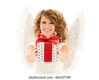 people, holidays, christmas, birthday and religious concept - happy young woman with angel wings holding gift box over white background