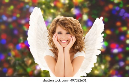 people, holidays, christmas and party concept - happy young woman or teen girl with angel wings over lights background
