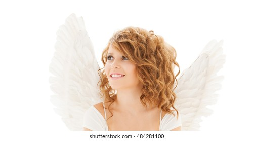 people, holidays, christmas and religious concept - happy young woman or teen girl with angel wings over white background