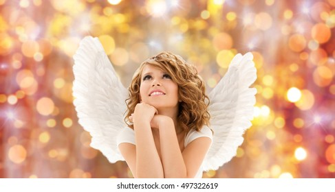 people, holidays, christmas and religious concept - happy young woman or teen girl with angel wings over lights background