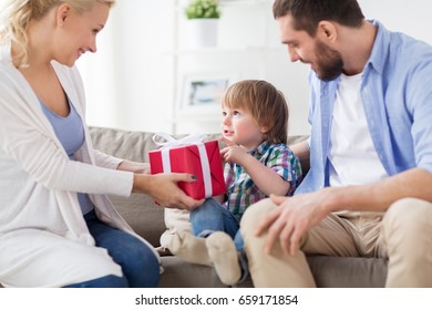 people and holidays concept - happy family with birthday gift at home