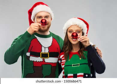 people and holidays concept - portrait of happy couple in santa hats making noses of red christmas balls at ugly sweater party