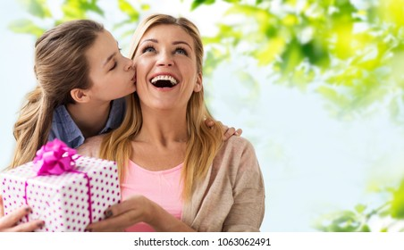 people, holidays and family concept - daughter kissing happy mother and giving her birthday present over green natural background